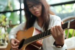 Abschluss oben junge Frau, die klassische Gitarre für das Spielen von Musik aco verwendet Lizenzfreie Stockbilder