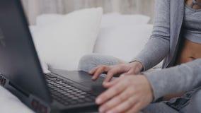 Abschluss oben Junges Mädchen in den Brillen, die auf dem Bett in einem hellen Raum und auf die Arbeit im Laptop konzentriert sit stock footage