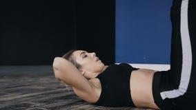 Abschluss oben Lügen der jungen Frau auf dem Boden und den Pumpen drücken an der Turnhalle Die Frau strebt herein Sport an stock video