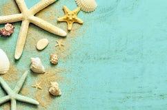 Abschluss oben Starfish, Muscheln und Sand auf einem hölzernen blauen Hintergrund stockfoto