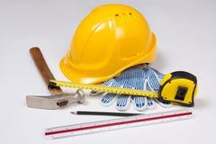 Abschluss oben von Arbeitswerkzeugen des Erbauers und von gelbem Sturzhelm über Weiß Lizenzfreie Stockfotografie