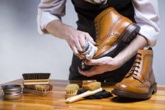 Abschluss oben von bemannt die Hände, die Luxuskalb-Leder Brogues mit speziellem Zubehör, Schuh-Wachs und Werkzeugen säubern lizenzfreie stockbilder