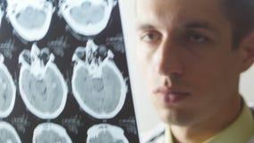 Abschluss oben von Doktor überprüft einen Schnappschuß der magnetischen Resonanz- Darstellung stock video