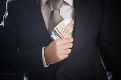 Abschluss oben von Geschäftsmann Handversteckendes Geld in seiner Anzugsjackentasche Stockfotografie