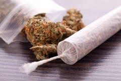 Abschluss oben von getrockneten Marihuanablättern und -gelenk Lizenzfreie Stockfotos