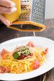 Abschluss oben von Händen in den Handschuhen reiben Käse auf einer Reibe über spaghet Lizenzfreie Stockfotos