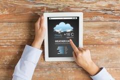 Abschluss oben von Händen mit Wetter warf auf Tabletten-PC Stockfotografie