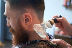 Abschluss oben von hairdresses arbeiten für einen attraktiven jungen blonden Mann am Friseursalon lizenzfreie stockfotografie