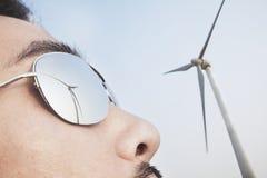 Abschluss oben von jungem bemannt Gesicht mit der Reflexion der Windkraftanlage in seiner Sonnenbrille Lizenzfreie Stockfotos