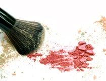 Abschluss oben von zerquetscht erröten auf weißem Hintergrund und kosmetischer Bürste lizenzfreies stockbild