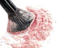 Abschluss oben von zerquetscht erröten auf weißem Hintergrund und kosmetischer Bürste lizenzfreie stockbilder