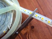 Abschneiden von unnötigen Stücken von LED-Band stockbilder