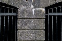 Abschnitt der konkreten strukturierten Wand mit anliegenden Metallkäfigen Stockfotografie