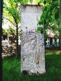 Abschnitt von Berlin Wall umgab durch Grün lizenzfreie stockfotografie