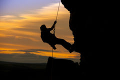 Abseil sunset. Rock climbing silhouette against a orange sunset in summer on a rock face Royalty Free Stock Image