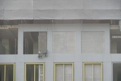 abseiling的建筑工人涂灰泥两个人 库存照片
