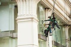 abseiling从一个高楼的玻璃清洁剂 库存照片