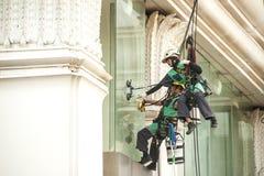 abseiling从一个高楼的玻璃清洁剂 免版税库存图片