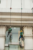 abseiling从一个高楼的玻璃清洁剂 图库摄影