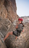Abseiling. A teen girl abseils down the side of a mountain Stock Images