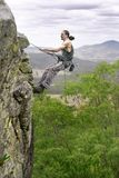 Abseiling. Man abseils down cliff with nice view behind royalty free stock photos