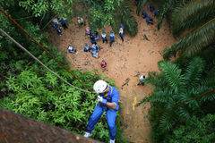 Abseiling Course. A man just have abseiling course while his team waiting below stock photo