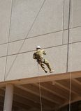 Abseiling down the wall. Guy in defence force camouflage fatigues abseiling down a wall royalty free stock photos
