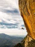 Abseiling eine negative gelbe Felsenwand mit Bergen auf backgrou nach Klettern Stockfotos