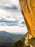 Abseiling en negativ guling vaggar väggen med berg på backgrou Royaltyfri Foto