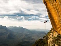 Abseiling en negativ guling vaggar väggen med berg på backgrou efter vaggar klättring Royaltyfri Fotografi