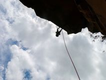 Abseiling a negative sanstone rock wall with blue sky on background stock photography