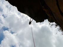 Abseiling a negative sanstone rock wall with blue sky on background - view from bellow stock photos