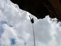 Abseiling a negative sanstone rock wall with blue sky on background - view from bellow. In Brazil stock image