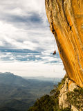 Abseiling a negative yellow rock wall with mountains on backgrou Royalty Free Stock Photo