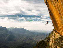 Abseiling a negative yellow rock wall with mountains on backgrou after rock climbing Royalty Free Stock Photography