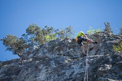 Abseiling from a rock. Man comes down from peak. stock photo