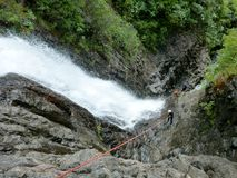 Abseiling next to Waterfalls. Abseiling team watching their partner set the rope next to a waterfall stock image