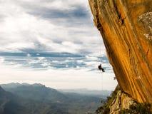 Abseiling una pared amarilla negativa de la roca con las montañas en fondo después de escalada Imagenes de archivo