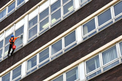 Abseiling Window Cleaner. An abseiling window cleaner, hanging from a rope on an office block stock photo