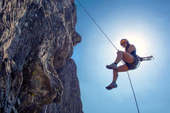 Abseiling woman. Young, tough, woman, abseiling from a steep rock, just in front of the sun royalty free stock images