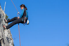 Abseiling. Young woman abseiling steep rock face Stock Photography