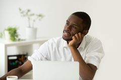 Absent-minded african intern dreaming of successful business and. Dreamy african american young man thinking of new idea at workplace, black lazy worker avoiding Stock Images