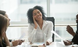 Absent-minded distracted black businesswoman dreaming smiling at. Absent-minded distracted black businesswoman dreaming of success and happiness at corporate Stock Photography