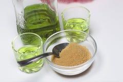 Absint är grön I en flaska och hällt in i exponeringsglas Farin för caramelizing av drinken På en vit bordsskiva Arkivfoto