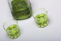 Absint är grön I en flaska och hällt in i exponeringsglas På en vit bordsskiva Arkivfoto