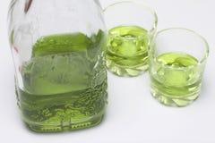 Absint är grön I en flaska och hällt in i exponeringsglas På en vit bordsskiva Royaltyfri Bild