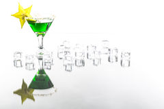 Absint in cocktail glass decorated with ice cube and carambola. Absinth in cocktail glass with reflection Royalty Free Stock Photo