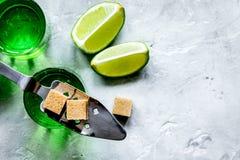 Absint i exponeringsglas med limefruktskivor på bästa sikt för stenbakgrund Arkivbild
