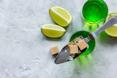 Absint i exponeringsglas med limefruktskivor på bästa sikt för stenbakgrund Royaltyfri Foto