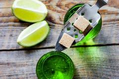 Absint i exponeringsglas med limefruktskivor på bästa sikt för träbakgrund Royaltyfri Foto